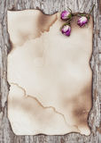 Dry roses on the old paper and wooden background Stock Photo