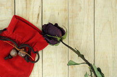 Dry roses with red small bag on wood pattern background Royalty Free Stock Photography