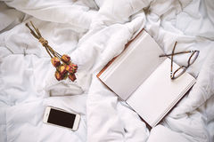 Dry roses, smartphone and vintage notebook on bed Royalty Free Stock Photo