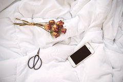 Dry roses, smartphone and vintage scissors on bed Stock Photography