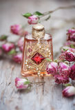 Dry roses and vintage perfume bottle on  old wood background Royalty Free Stock Photos