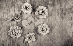 Dry roses and a wooden heart. Dead flowers and love. Romantic concept. Monochrome Royalty Free Stock Images