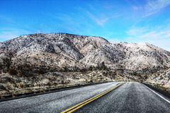 Dry Run - Mojave desert, California. The dry arid wind whips past a lonely desert road, making its way up and over the mountains and through the valleys across a Royalty Free Stock Images