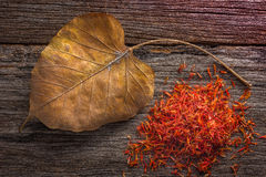 Dry Safflower with leaf  on grunge wooden background. Royalty Free Stock Photography
