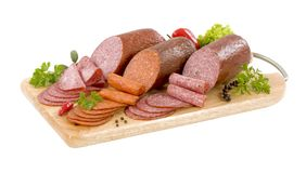 Dry salami. Three dry salami sausages on a cutting board stock images