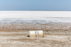 Dry salt lake with a fallen container. Dry salt lake with a fallen concrete container for garbage Royalty Free Stock Images