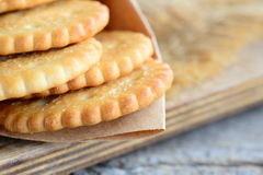 Dry salty cracker biscuits in a wrapping paper and wooden board. Crunchy savory cookies snack idea for children or adults Stock Photos