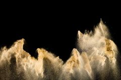 Dry sand explosion. Brown colored sand splash against  black background stock photography