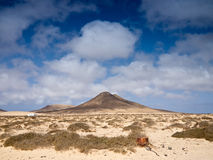 Dry sandy dunes and lonely mountain Stock Images