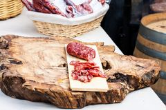 Dry sausage and Italian salami on raw wood cutting board stock photo