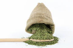 Dry savory. Spilling dry savory from burlap bag over wooden spoon for dosing when cooking Stock Image