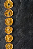 Dry slices of citrus fruits on a black slate background. Royalty Free Stock Photos