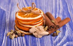 Dry slices of orange, cinnamon, pimento and cardamom, on a blue wooden background. Aromatic spices. Christmas Stock Image