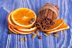 Dry slices of orange, cinnamon, pimento and cardamom, on a blue wooden background. Aromatic spices. Christmas Royalty Free Stock Photography