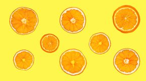 Dry slices of orange isolated on yellow background. A collage of dried orange. Royalty Free Stock Photos