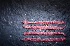 Dry smoked pork sausage on the stone slab. Royalty Free Stock Photography
