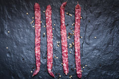 Dry smoked pork sausage on the stone slab. Royalty Free Stock Images