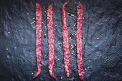 Dry smoked pork sausage on the stone slab. Royalty Free Stock Images