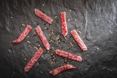 Dry smoked pork sausage on the stone slab. Stock Images