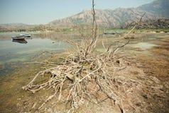 Dry soil around salt lake Bafa with fishermen boats, Turkey. Royalty Free Stock Photo