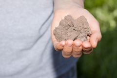 Dry soil in hand Stock Photos