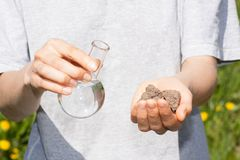 Dry soil in hand and a flask with water Stock Photography