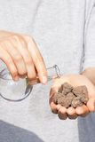 Dry soil in hand and a flask with water Royalty Free Stock Photography