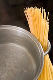Dry spaghetti with boiling water in a pan. Dry spaghetti standing next to a metal pan with boiling water and a dark background Stock Photo