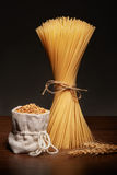Dry spaghetti pasta, burlap bag of grains and wheat ears Royalty Free Stock Images