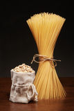 Dry spaghetti pasta and burlap bag of oatmeal on table Royalty Free Stock Image