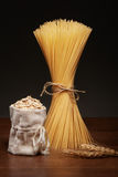 Dry spaghetti pasta, burlap bag of oatmeal and wheat ears Royalty Free Stock Image