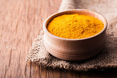Dry spice turmeric in a wooden bowl close-up Stock Images