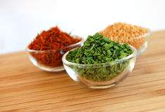Dry Spices. Three glass containers with saffron, mustard seed and chive on a wooden cutting desk Stock Images