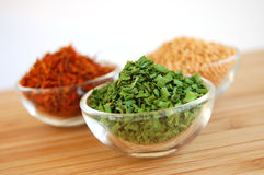 Dry Spices. Three glass containers with saffron, mustard seed and chive on a wooden cutting desk Royalty Free Stock Photography