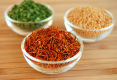 Dry Spices. Three glass containers with saffron, mustard seed and chive on a wooden cutting desk Royalty Free Stock Photo