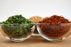 Dry Spices. Three glass containers with saffron, mustard seed and chive on a wooden cutting desk with a white background Stock Photo