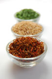 Dry Spices. Three glass containers with saffron, mustard seed and chive on a white background Stock Images