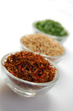 Dry Spices. Three glass containers with saffron, mustard seed and chive on a white background Royalty Free Stock Photography