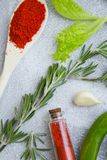 Set of spices and herbs on light stone background. Dry spices and herbs in a wooden spoon and glass jar with fresh herb springs, chili pepper and garlic on a Stock Images