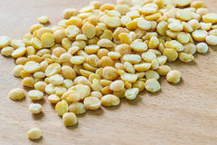 Dry split peas scattered on the kitchen wooden Board royalty free stock photos