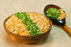 Dry split yellow and green peas in a clay bowl for pea porridge or soup. Split dried peas are used to make traditional dishes: pudding, porridge and soup in many stock image