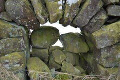 Dry stone wall. Archway filled in the centre Stock Images
