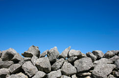 Dry stone wall on blue sky Stock Images