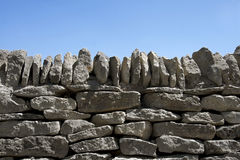 Dry-stone wall and blue sky. A dry stone wall against clear blue sky. Space for text Stock Photos