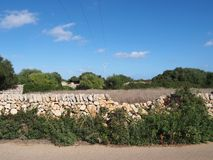 Dry stone wall running alongside a county road and fields in typical menorca countryside. A dry stone wall running alongside a county road and fields in typical stock photo