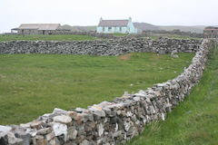 Dry stone walls and cottage. Dry stone walling on Fair Isle in the Shetland Isles, Scotland Royalty Free Stock Photo
