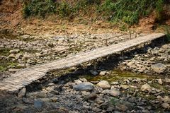 Dry stony river bed with Bamboo bridge. Dry stony river bed Sunny summer day Royalty Free Stock Images