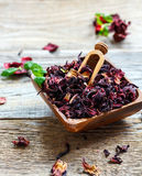 Dry tea Hibiscus in a square wooden bowl. Stock Images