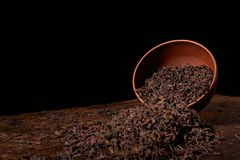 Dry tea leaves in clay bowl on black background. selective focus. Dry tea leaves in clay bowl on black background on wooden table royalty free stock photos