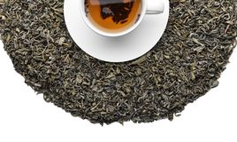 Dry tea leaves and cup with hot beverage on white background, top view stock image